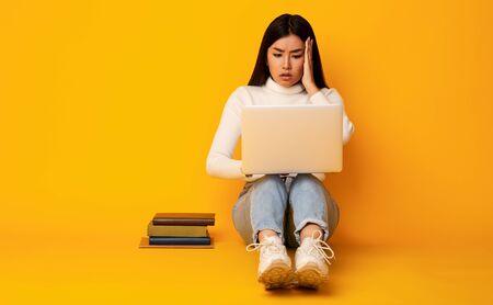 Studentessa delusa che guarda il laptop, che ha problemi a prepararsi per le lezioni, sfondo giallo dello studio