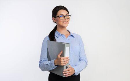 Freundliche Geschäftsfrau, die Ordner mit dem Geschäftsbericht hält, der in die Kamera auf weißem Studiohintergrund lächelt. Buchhaltung