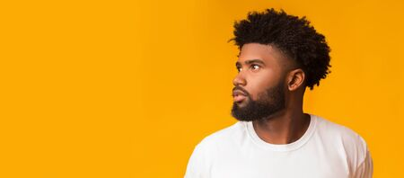 Thoughtful afro guy looking at copy space over orange background, panorama