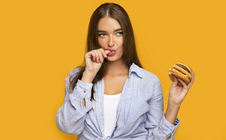 Hungry Girl Holding Burger Licking Fingers Standing Over Yellow Studio Background.