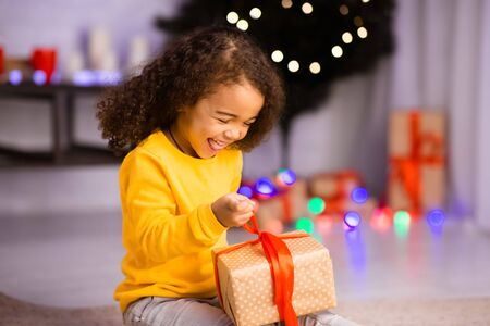 Emotional happy afro girl opening desired Christmas gift at home Standard-Bild