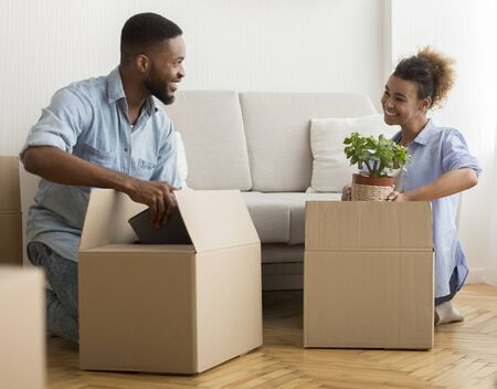 Joyful Afro Spouses Packing Boxes Together Sitting On Floor At Home. Selective Focus