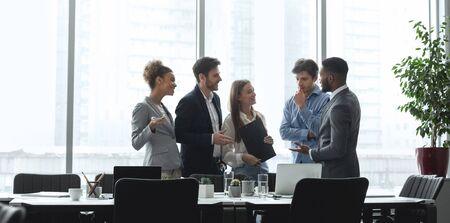 Equipo de gestión diverso hablando en la sala de conferencias, discutiendo ideas contra las ventanas de la oficina, panorama