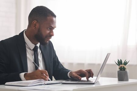Concentrated african business clerk making notes, using laptop in his office, empty space Standard-Bild