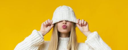 Blonde young woman pulling down knitted white hat, showing kissing lips, yellow studio background, panorama