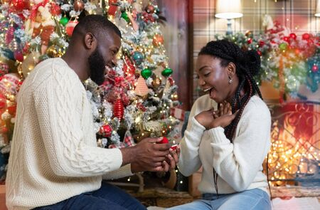 Loving man giving engagement ring to his happy girlfriend near Xmas tree at home, proposing to marry him