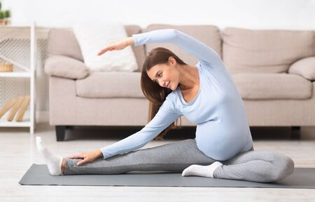 Pregnant Woman Stretching Arms And Legs, Doing Prenatal Workout At Home On Yoga Mat. Selective focus Banco de Imagens
