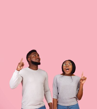 Amazed african american man and woman pointing fingers upwards and looking at free space on pink studio background