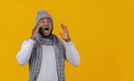 Stunned black winter man talking by phone, looking at free space, got shocking news, yellow background