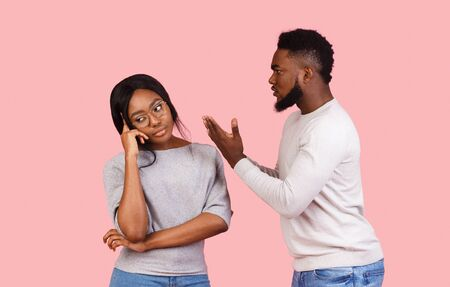 Afro couple fighting over pink studio background, man screaming, annoyed woman looking aside