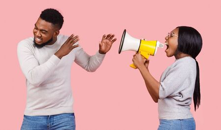 African american girl shouting through megaphone at her man, pink background Stockfoto - 134409607