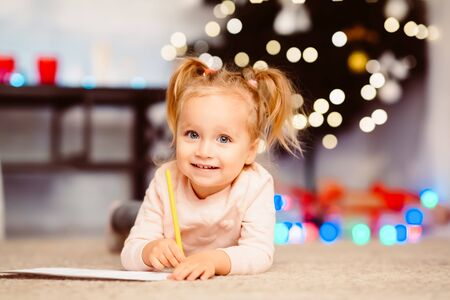 Adorable little girl writing letter to Santa Claus, lying on floor, free space