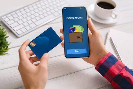 Uomo che utilizza lo smartphone con l'applicazione di portafoglio digitale che effettua il pagamento dalla carta di credito sul posto di lavoro in ufficio, primo piano