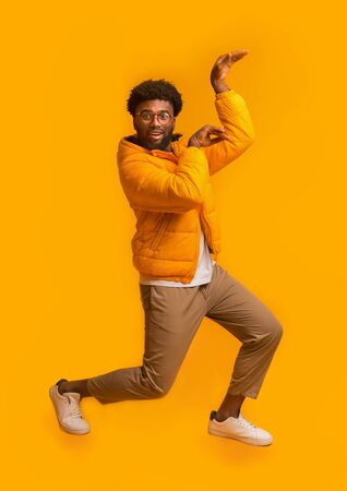 Funny black guy fooling, dancing in egypt style, wearing glasses and winter jacket on orange studio background