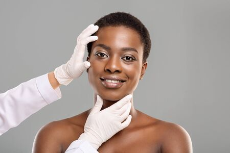 Cosmetic Surgery Concept. Doctor Examining Young Afro Womans Face Over Grey Background, Copy Space Standard-Bild