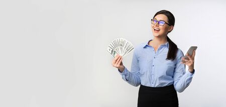 Business Woman Holding Mobile Phone And Money Cash Winking At Camera Standing Over White Studio Background. Panorama, Empty Space 免版税图像