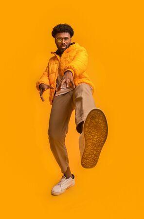 Black funny guy in winter jacket showing beast, stepping on camera, orange background