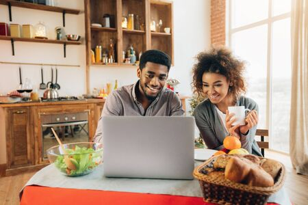 Glückliches afroamerikanisches Paar, das Laptop in der Küche verwendet, Hochzeit und Flitterwochen plant., Panorama, Kopierraum