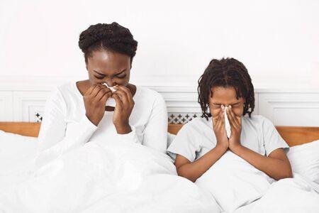Síntomas de alergia. Infeliz familia afro usando pañuelos de papel mientras se suena la nariz y estornuda Foto de archivo