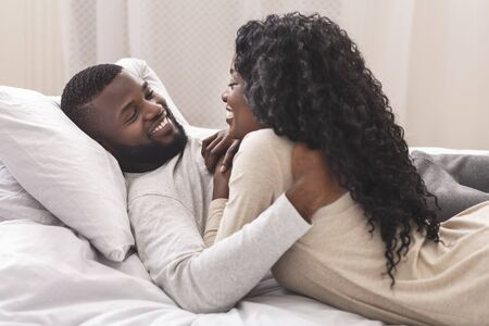 Smiling african american couple having fun in bed, embracing and flirting with each other, closeup