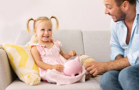 Millennial Father Teaching His Daughter How To Save Money. Cute girl sitting with piggy bank Фото со стока