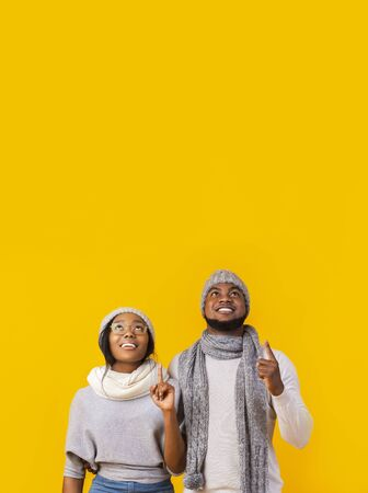 Unbelievable sale. Interested african american winter man and woman pointing fingers upwards and looking at free space on yellow studio background