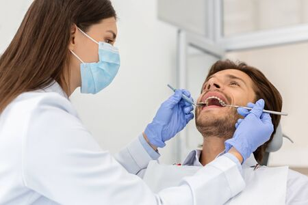 Man making check up in modern dental clinic, female doctor checking his teeth Stock Photo