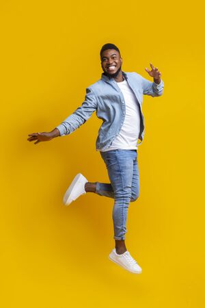 Portrait of funny black man jumping on yellow background with euphoric face expression, free space for text