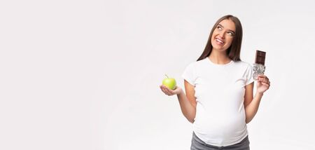 Pregnant Lady Holding Apple And Chocolate Choosing Between Healthy And Unhealthy Products Standing Over Gray Studio Background. Panorama, Copy Space Stok Fotoğraf