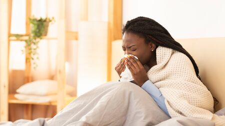 Influenza. Sick Black Girl Blowing Runny Nose Sneezing Sitting In Bed At Home. Panorama, Free Space For Text Stock Photo