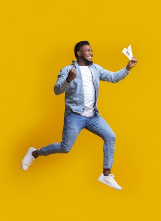 Cash back. Euphoric millennial black guy jumping with dollar banknotes in hand over yellow background, free space