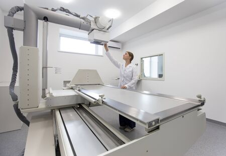 Laboratory worker tuned modern X-ray equipment, copy space