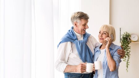 Happy senior woman talking on phone near window, husband embracing wife and looking at her, free space Imagens