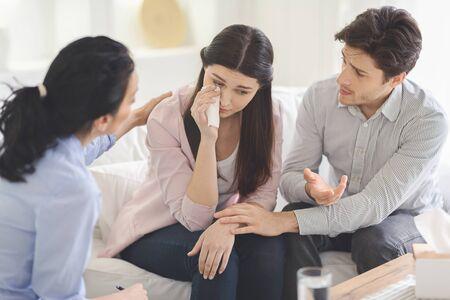 Psychotherapeut en jonge man die depressieve huilende vrouw ondersteunt tijdens therapie Stockfoto