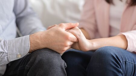 Man and woman holding hands, supporting each other during session with psychologist, cropped