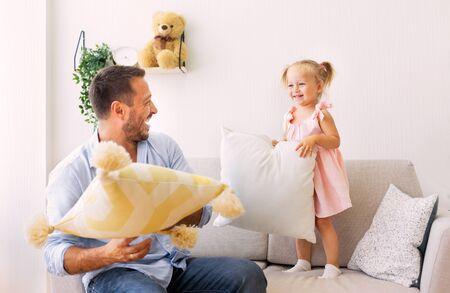 Concetto di mattina di famiglia. Papà e figlia giocherelloni litigano con i cuscini in camera da letto