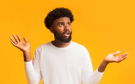 Excited african man raising his hands up, being surprised to see shocking news, copy space