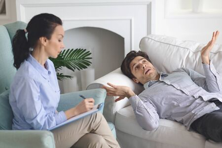 Puzzled man laying on coach at psychologist cabinet, sharing thoughts with specialist, free space