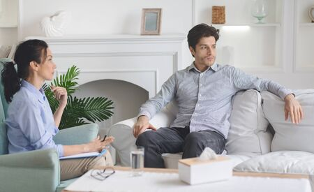 Frustrated sad man looking aside during session with psychotherapist, having hard period in his life, copy space Фото со стока