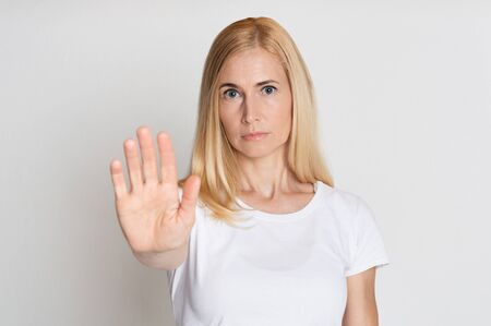 No means no. Woman showing stop gesture, standing with stretched hand over grey background Фото со стока