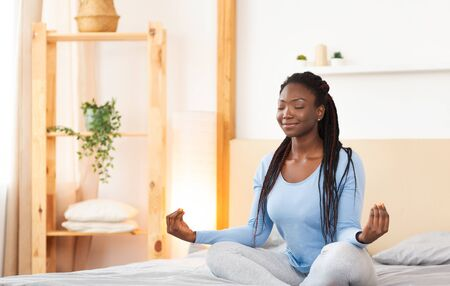 Relaxation. Peaceful Afro Lady Sitting In Lotus Position Meditating In Bed At Home. Copy Space, Selective Focus