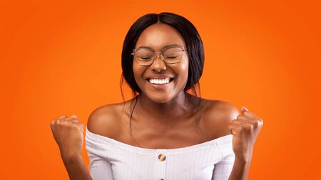 Joy. Happy Black Woman Gesturing Yes Celebrating Something Standing Over Orange Studio Background. Panorama Imagens