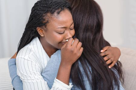 Friendship and consoling. Unrecognizable black woman hugging her crying friend at home, comforting and expressing support, closeup