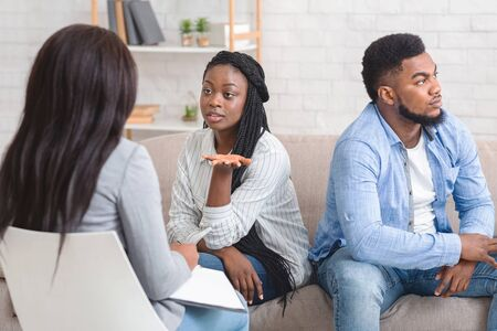 Marriage Therapy Session. Afro Wife Sitting Next To Her Displeased Husband And Talking To Counselor About Problems In Their Relasionship.