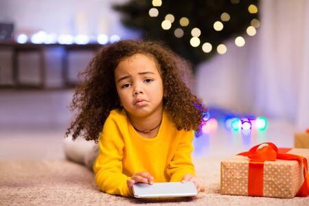 I wanted doll. Sad african little girl with unwanted Christmas gift cellphone, free space