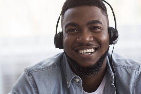 Operador de servicio al cliente. Retrato de alegre gerente de centro de llamadas afroamericano en auriculares, primer plano