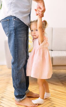 Image Recadrée De Papa Et Fille Dansant à La Maison. Adorable petite fille debout sur les pieds du père