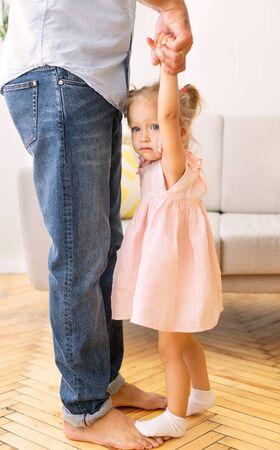 Zugeschnittenes Bild von Papa und Tochter, die zu Hause tanzen. Entzückendes kleines Mädchen, das auf den Füßen des Vaters steht