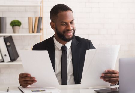 Happy black businessman checking reports in modern office, satisfied by results of his company, empty space