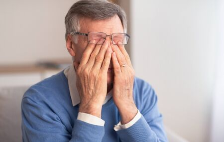 Eyesiht Problem. Unrecognizable Senior Man Massaging Tired Eyes Trying To Relieve Pain Sitting On Couch At Home.
